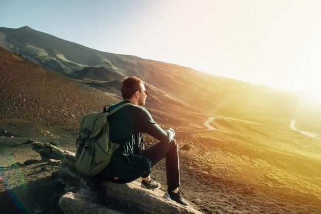 man-with-rucksack-sitting-rock-sunset-volcano-etna-mountain-sicily_8353-6518-6578881-6414425-3315507